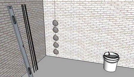 Нанесение штукатурного раствора под маяк на стене