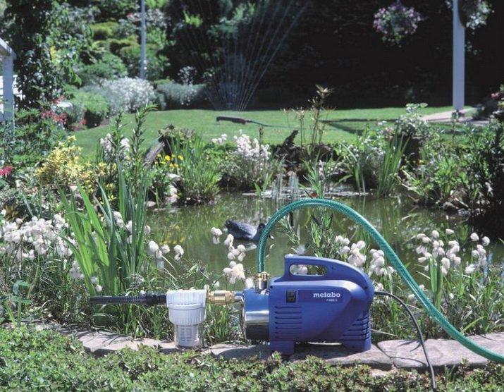 Насос в саду поливающий огород и растения