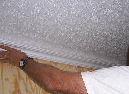 Плинтусом закрываются края наклеенной на потолке плитки
