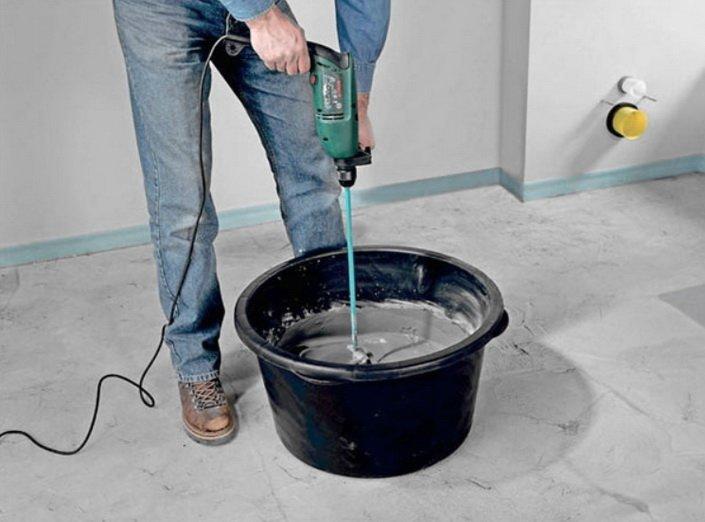 С помощью дрели готовится смесь для шпатлевки стен
