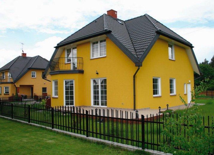 Фасад частного дома покрашен желтой краской