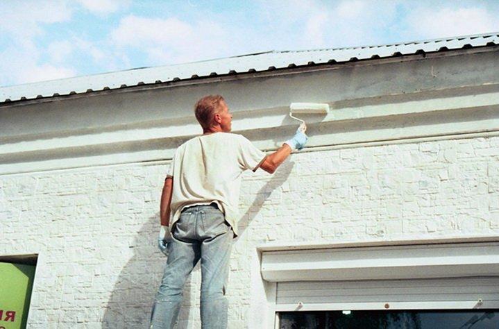 Краска наносится с помощью валика на фасад здания