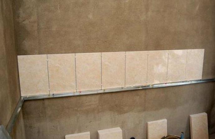 Первый ряд плитки уложенный на стену
